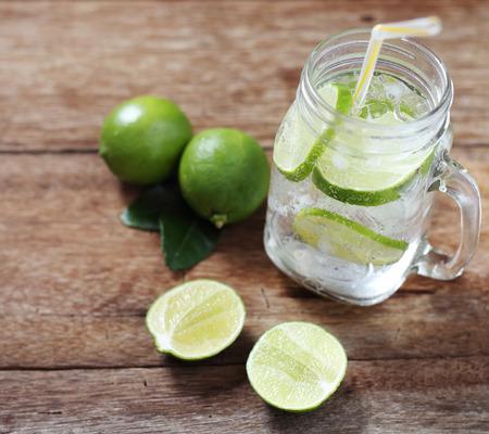 lemon juice: Lemon juice glass and fresh lemons on wood table background