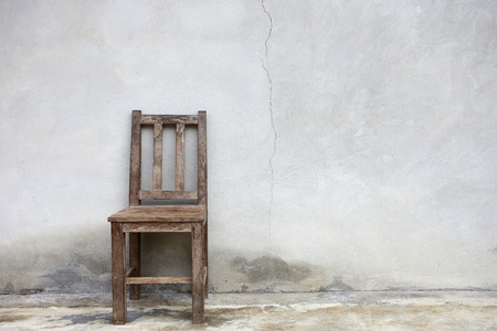 Old chair against old wall background Stock Photo