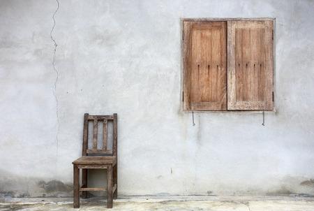 silla de madera: Silla vieja contra la pared vieja con la ventana de fondo Foto de archivo