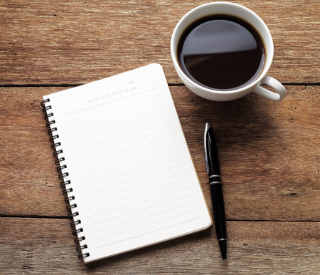 notebook computer: Open a blank white notebook, pen and cup of coffee on wood desk