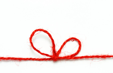 Red string bow on a white background.
