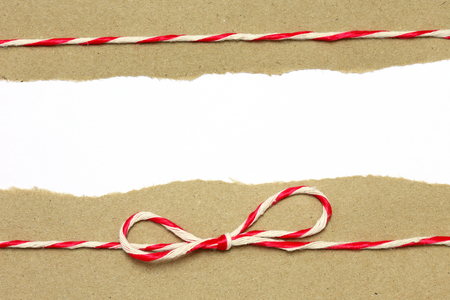 red bow: String red and white on brown wrapping paper with copy space background Stock Photo