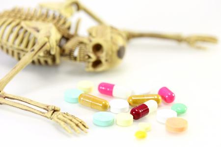 esqueleto: esqueleto con drogas en el fondo blanco sobre el concepto de la dosis.