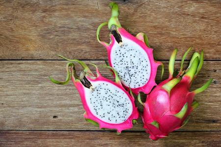 Juicy pink pitaya on wooden table closeup