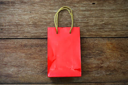 paper bag: Red Paper bag on a wooden texture background