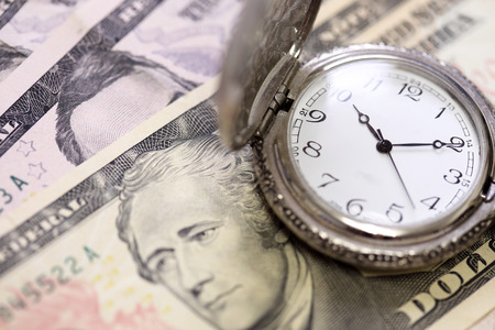 managing money: Time is money watch clock on bank note Stock Photo