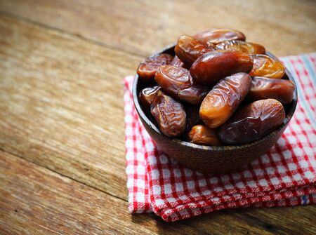 Dates palm fruit in a wooden bowl closeup on wooden background