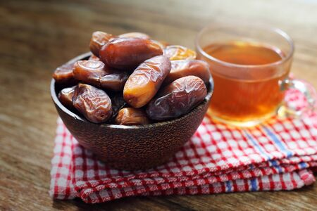 arabian food: Date-palm in wood bowl with cup of tea on wood table Stock Photo