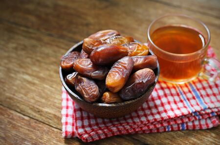 Date-palm in wood bowl with cup of tea on wood table 写真素材