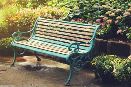 Vintage Bench in flower garden with vintage light filter