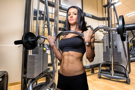 sixpack: Woman bodybuilder lifting curl bar barbell in the modern gym.