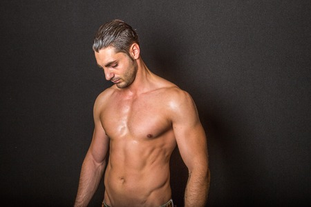 bronzed: Portrait of handsome male fitness model black background.