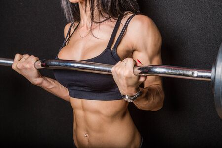 muscularity: Body of a muscular female bodybuilder lifting a barbell with a black background. Stock Photo