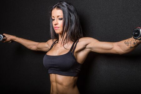 muscularity: Muscular female bodybuilder exercising with dumbbell weights, black studio background.