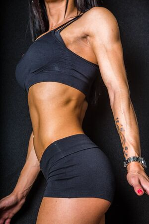 midriff: A female fitness model showing her abdominal muscles. on black background.