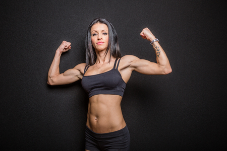 considerable: Attractive young woman body builder in sports bra and shorts standing up and flexing her considerable muscles, black background. .
