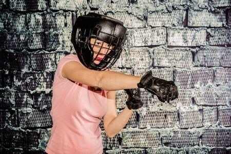 f�minit�: Belle femme au cours de sa formation pour le sport de combat. Concept de force, la concentration, la d�termination, mais aussi la f�minit�. La femme porte un casque de protection et des gants Banque d'images