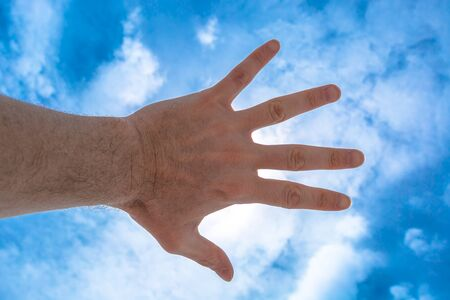 vision problems: Hand of a man reaching out against a cloudy blue sky, covering the sun. Concept of business and communication of self-confidence. Concept of focus on yourself and clear vision of the problems.