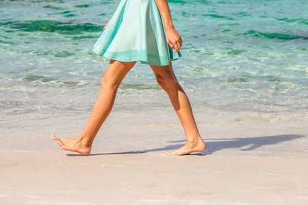 feet naked: Sexy woman dressed with green skirt walking bare foot on the beach shore. Closeup of her tanned naked shaved legs. Closeup detail of female feet and white sand.
