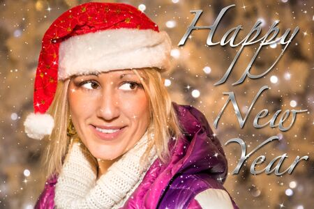 ecard: Portrait of beautiful woman with Christmas Santa Claus hat on shining lights background. Happy New Year 2016 message as greetings e-card or banner. Archivio Fotografico