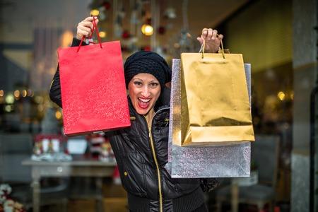 compras compulsivas: Antojos mujer que sostiene brillante bolsas de compras durante las ventas de Navidad en la ventana de la tienda.