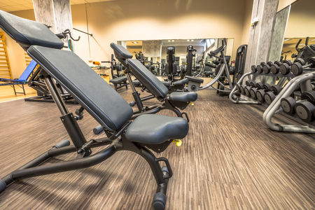workouts: Panoramic interior view of modern equipment in the gym with mirrors on the walls, machines for sport, fitness and wellness.