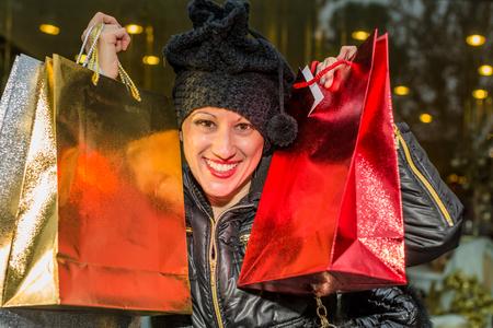 compras compulsivas: Retrato de una mujer feliz celebraci�n de brillantes bolsas de compras para la Navidad.