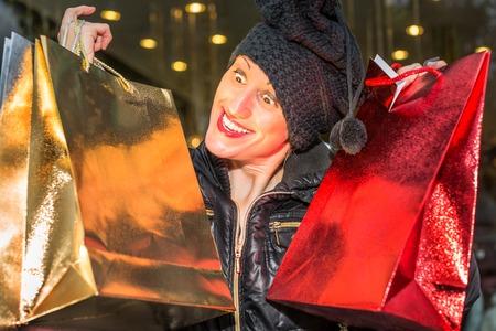 compras compulsivas: Retrato de una mujer antojos compulsivos celebración brillantes bolsas de compras para la Navidad.
