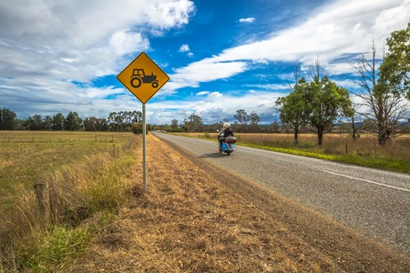 tractor warning: Motorcyclist on the road with tractors crossing sign on the tasmanian country road, Australia.