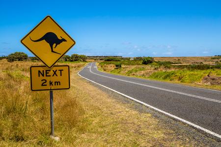 señales preventivas: Señal de peligro de canguro cruce en la carretera nacional Austalian.