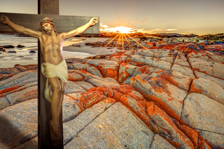 redemption: Cross of Christ on a blood red cliff, ocean and cloudy sunrise. The sun rays light the wooden crucifix. Concept of resurrection and hope. Metaphor about the natural red rocks that look like bloody scars of mankind sins, sunlight as afterlife redemption.