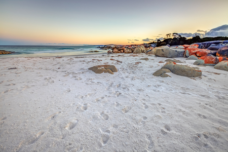 helens: Scenic and pristine white sandy beach with turquoise crystal waters and orange lichen covered granite boulders at sunset. The Gardens in the Bay of Fires consevation Area, east coast of Tasmania Stock Photo
