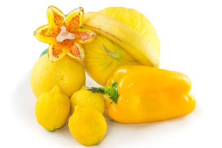 yellows: Still life of assorted bright yellow fruits and vegetables with a glass flower, isolated on white .