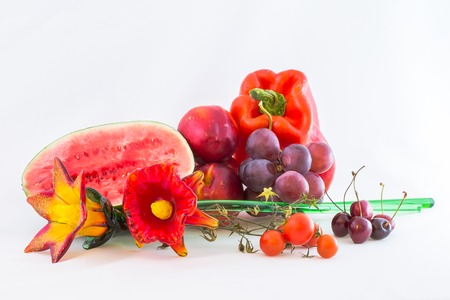 grouping: Group of red fruits and vegetables with glass flower, isolated on white .