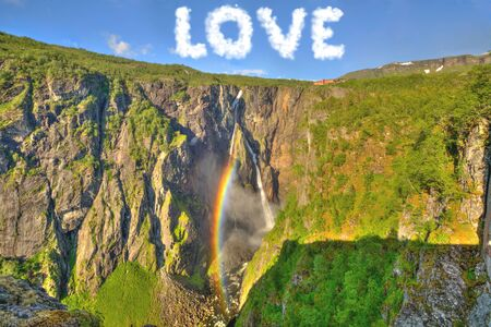 clean environment: Cloud shaped word of love in the sky, above rainbow which shines on the waterfall. Concept of love for nature, new beginning, divine providence from the sky, spirituality, Valentine, clean environment Stock Photo