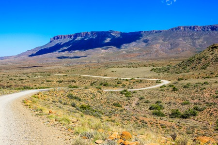 Dirt road with blue sky, Karoo National Park in the summer, Western Cape province of South Africa. Stok Fotoğraf