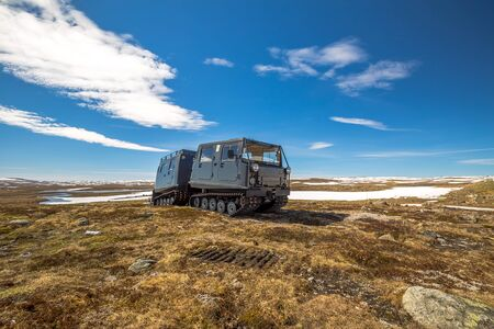 tracked: A snowcat tracked on snowy mountain landscape of the plateau Hardangervidda National Park in Norway, Europe. Right side view.