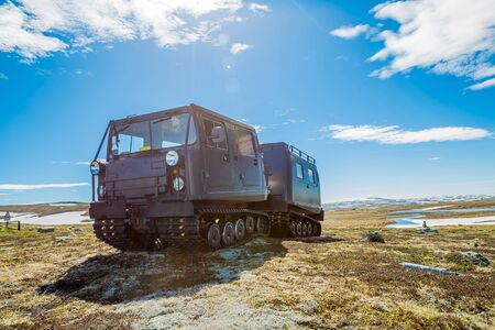 tracked: A snowcat tracked on snowy mountain landscape of the plateau Hardangervidda National Park in Norway, Europe. Left side view. Stock Photo