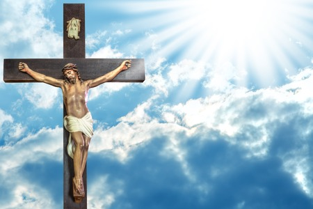 resurrected: Jesus Christ to paradise: cross of Jesus Christ on sky background with a shining celestial light from above. Stock Photo
