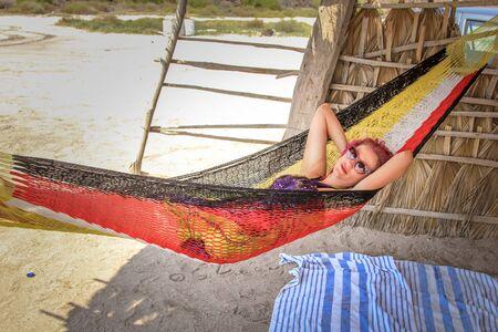 Young woman while relaxes on a hammock. A Conception Baja, California Sur, Mexico.