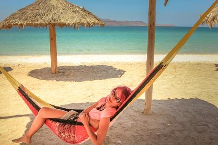 relaxes: Joven mujer se relaja en una hamaca en Playa Telecote. La Paz, M�xico, Baja California Sur. .