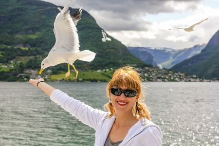 sognefjord: A young smiling woman sul ponte del traghetto feeds a seagull. Against the backdrop of the magnificent mountains of the Sognefjord in Norway. . Stock Photo