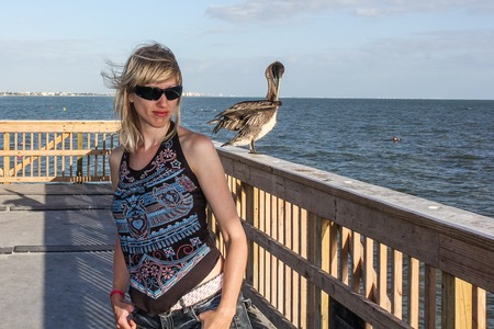 fishing pier: Beautiful young woman close to pelican on the fishing pier in Florida United States. Stock Photo