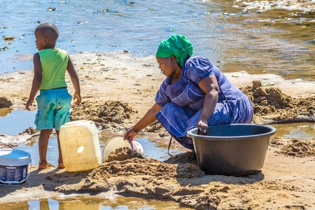 leading: African woman and child collecting water from the river on the road leading to UMkhuze Game Reserve, South Africa.
