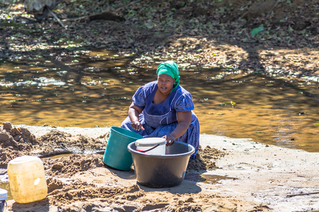 poor african: Poor african woman collecting water from the river on the road leading to UMkhuze Game Reserve, South Africa. Editorial