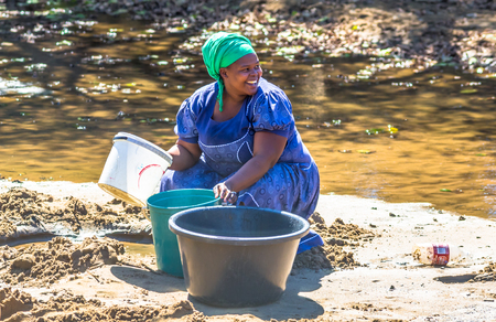 woman at work: African woman smiling collecting water from the river on the road leading to UMkhuze Game Reserve, South Africa.