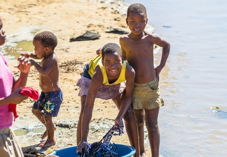 minors: African children washing their clothes to the river on the road leading to UMkhuze Game Reserve, South Africa.