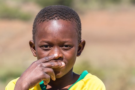 poor african: Portrait of a poor and thoughtful South African child on the road leading to UMkhuze Game Reserve, South Africa.