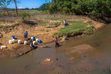 Arme Afrikaanse kinderen verzamelen water uit de rivier op de weg die leidt naar UMkhuze Game Reserve, Zuid-Afrika. Redactioneel