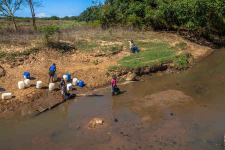 poor african: Poor African children gathering water from the river on the road leading to UMkhuze Game Reserve, South Africa. Editorial